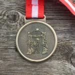 Bagsiden af en medalje fra H.C. Andersen Marathon 2013. Medaljen indeholder en illustration af H.C. Andersens eventyr: Kejserens nye klæder.